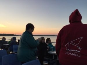 picture of the upper deck of a boat with students sitting and standing around looking away from the camera into a sunset. Student standing close to the camera is wearing a sweater with EUMASLI and a boat logo in red.